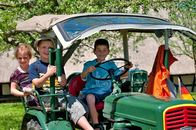 Kinder auf einem Traktor im Museumsdorf Kürnbach