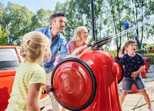 Familie bei den Feuerwehrautos im Ravensburger Spieleland