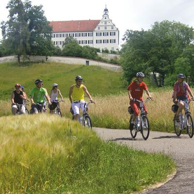 Radfahrer mit dem Schloss Mochental im Hintergrund