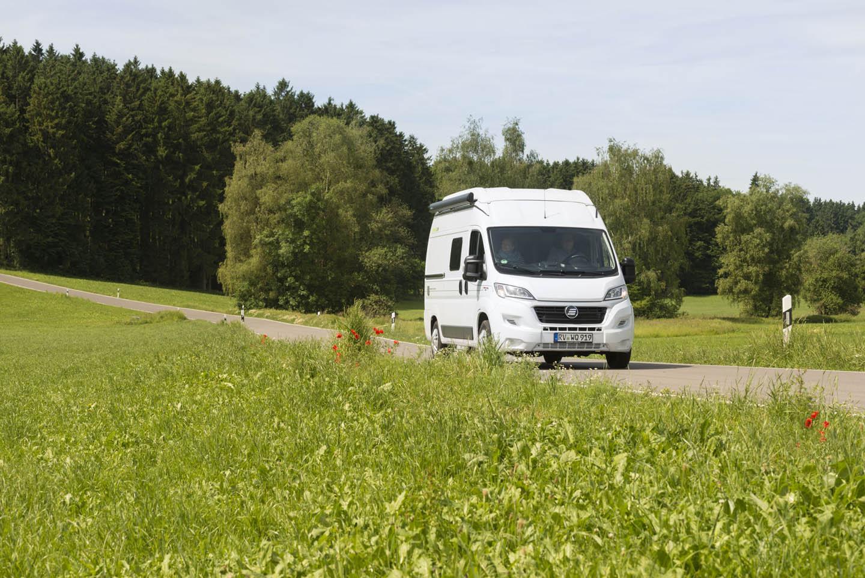 Reisemobil unterwegs, im Hintergrund ein Wald